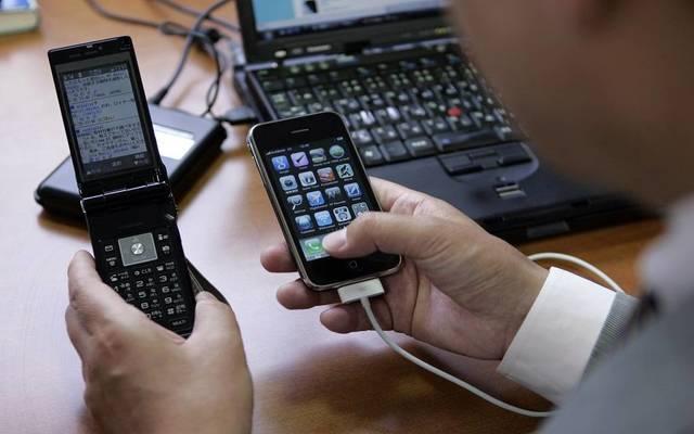 رجل يستخدم الهاتف النقال والثابت