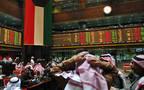 مستثمرين أمام شاشة التداول في سوق أبوظبي المالي