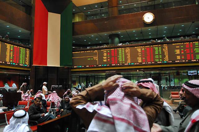 مستثمرون أمام شاشة التداول في سوق أبوظبي المالي