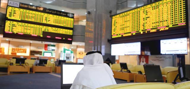متعاملون يتابعون الأسعار بقاعة سوق أبوظبي للأوراق المالية، الصورة أرشيفية