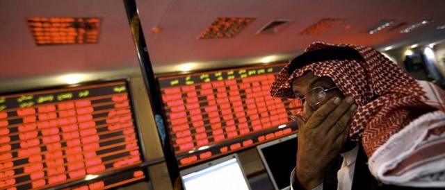 متعاملون يتابعون أسعار الأسهم بقاعة سوق قطر المالي