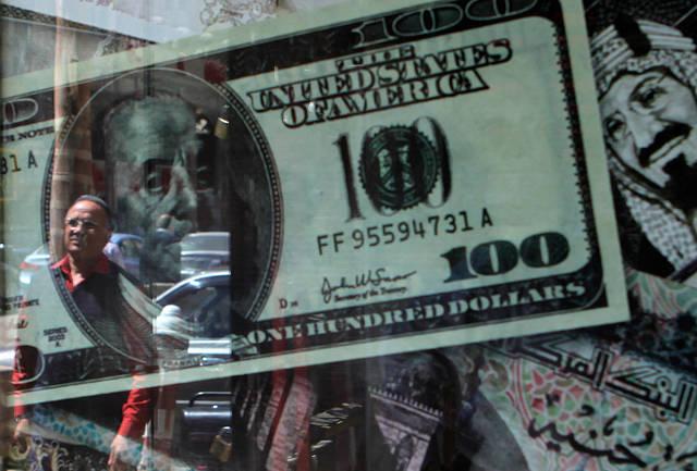 رجل يقف أمام لوحة عليها عدد من العملات تضم الريال السعودي والدولار الأمريكي والجنيه المصري