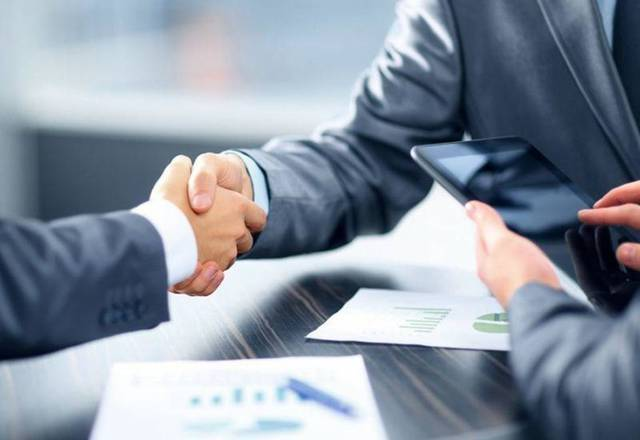 صورة تعبيرية عن توقيع صفقات الاستحواذ والاندماج