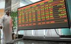 مستثمر يقف أمام شاشة التداولات ببورصة قطر