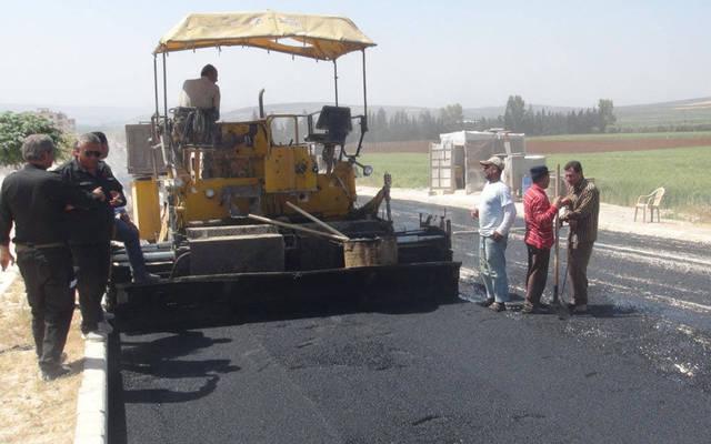 مجموعة من العمال يقومون برصف طريق
