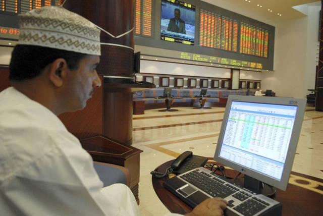مستثمر يتابع أسعار الأسهم بقاعة التداولات