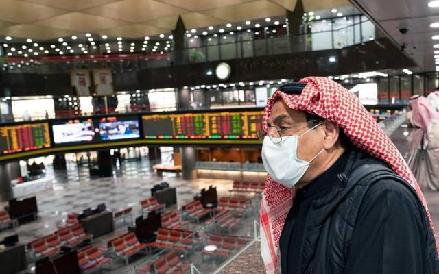 مستثمر يتابع التداولات ببورصة الكويت مُرتدياً كمامة الوقاية من الفيروسات
