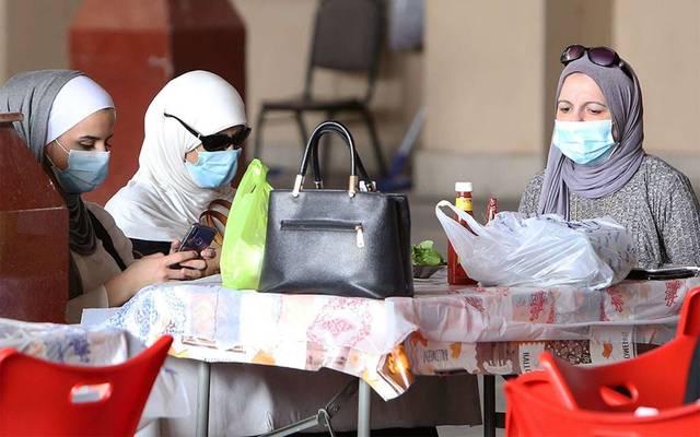 مواطنات ترتدين كمامات الوقاية من الفيروسات في أحد الأماكن العامة