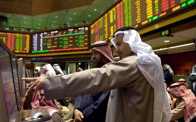 متعاملون يتابعون أسعار الأسهم الكويتية