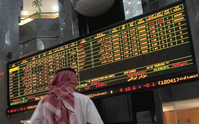 متعامل يتابع الأسعار بقاعة سوق أبوظبي للأوراق المالية