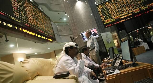 متعاملون يتابعون أسعار الأسهم بقاعة سوق أبوظبي للأوراق المالية