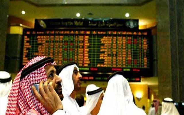 مستثمرون امام شاشة التداول في سوق أبوظبي للأوراق المالية