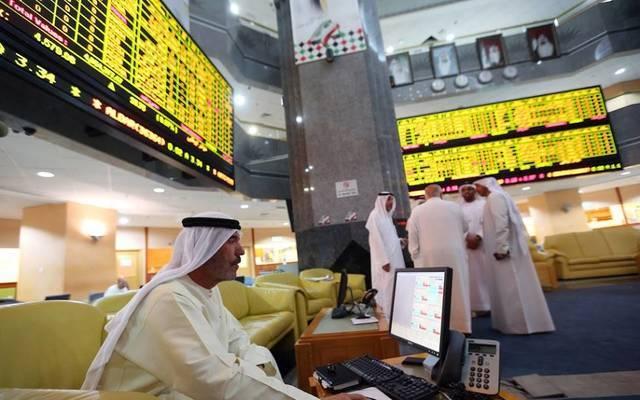 متعاملون يراقبون أسعار الأسهم بقاعة سوق أبوظبي المالي، الصورة أرشيفية