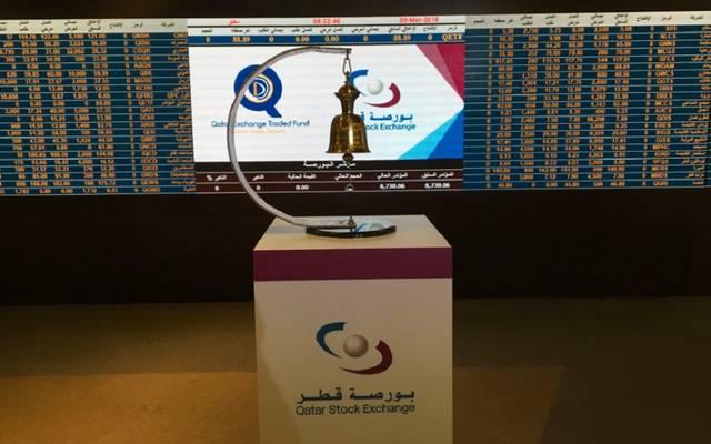 جرس التداول على منصة أمام شاشة الأسعار ببورصة قطر