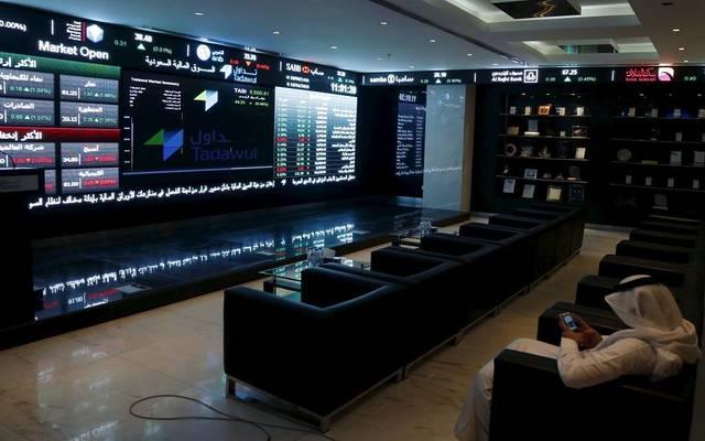 أحد المتعاملين يتابع شاشات التداول لسوق الأسهم السعودية