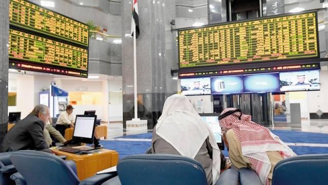 متعاملون يتابعون الأسعار بسوق أبوظبي للأوراق المالية