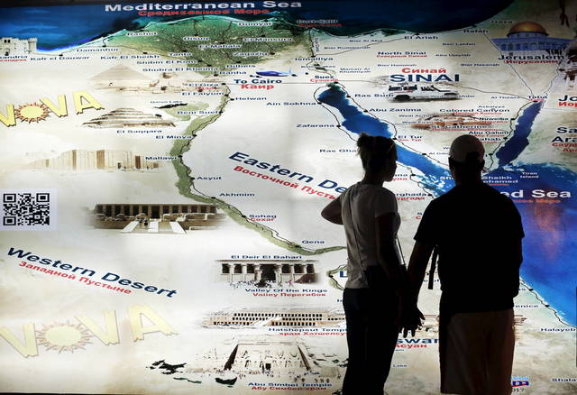 سائحان ينظران إلى مخطط للأماكن السياحية في مصر