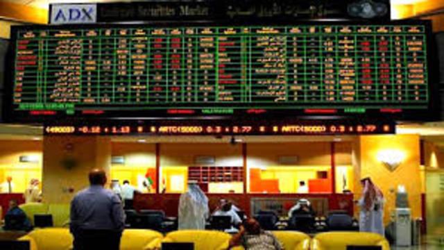 متعاملون يتابعون أسعار الأسهم بسوق أبوظبي للأوراق المالية، الصورة أرشيفية