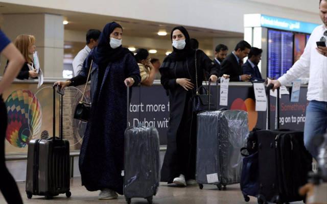 سيدتان يرتديا كمامة طبية في أحد المطارات العربية