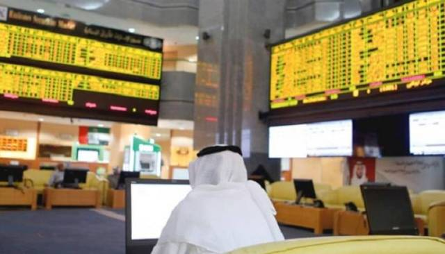 متعامل يتابع الأسعار بقاعة سوق أبوظبي المالي
