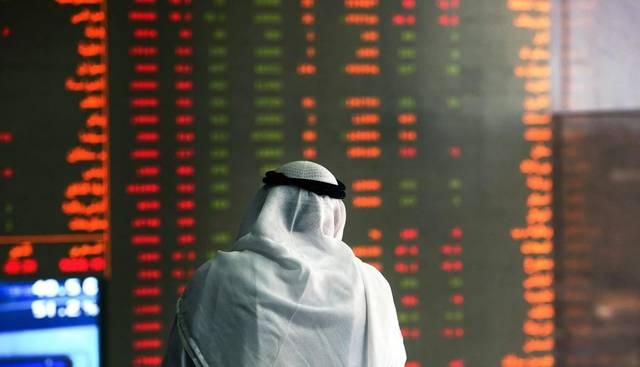 متعامل يتابع الأسعار بقاعة سوق الكويت المالي