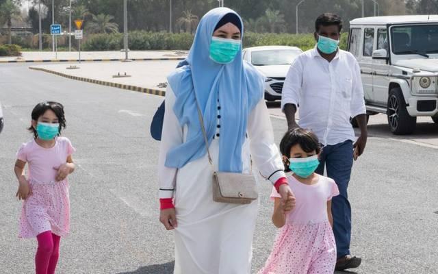 أسرة ترتدي كمامات الوقاية من الفيروسات في إحدى الطرقات