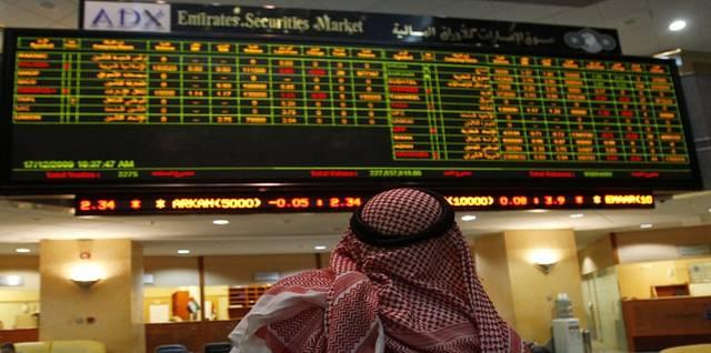 متعامل يتابع الأسعار على شاشة التداول بسوق أبوظبي المالي