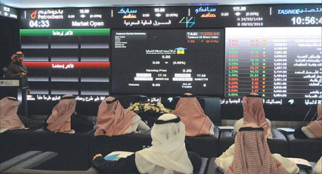 متعاملون يتابعون أسعار الأسهم بقاعة السوق السعودية