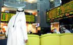 متعاملون يتابعون أسعار الأسهم بقاعة سوق أبوظبي المالي