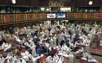 متعاملون يتابعون أسعار الأسهم بقاعة سوق الكويت المالي