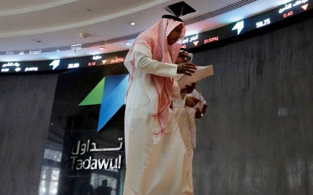 مواطنون يمرون أمام شاشة تعرض أسعار الأسهم السعودية