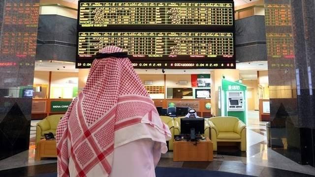متعاملون يتابعون أسعار الأسهم بسوق أبوظبي المالي