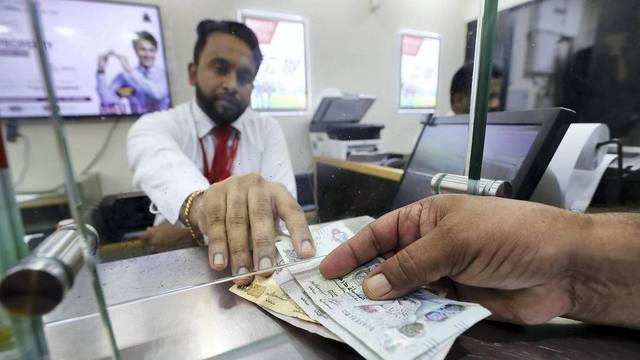 أحد الوافدين يقوم بعملية تحويل أموال بالإمارات