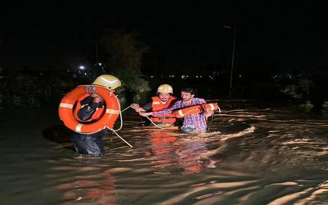 فرق الدفاع المدني خلال انقاذ احد العالقين بسبب السيول