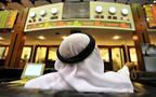 متعامل يتابع أسعار الأسهم بقاعة سوق دبي المالي