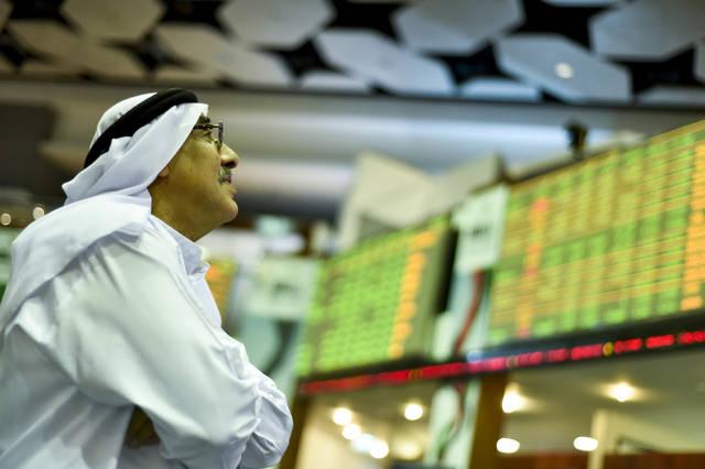 متعاملون يتابعون أسعار الأسهم بقاعة سوق دبي المالي، الصورة أرشيفية
