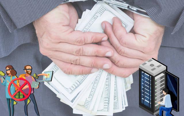 """صورة تعبيرية لشخص يمسك عملات فئة الدولار الأمريكي مع تقييد يديه - المصدر """"مباشر"""""""