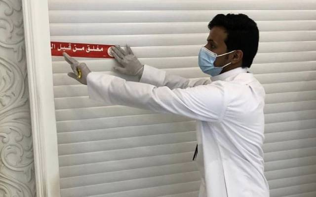 موظف ببلدية الكويت يقوم بإغلاق أحد المحال