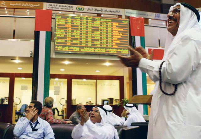 متعاملون يتابعون أسعار الأسهم بسوق دبي المالي، الصورة أرشيفية