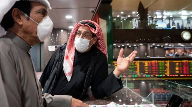 متداولون بالأسهم يتابعون الأسعار بقاعة سوق الكويت المالي