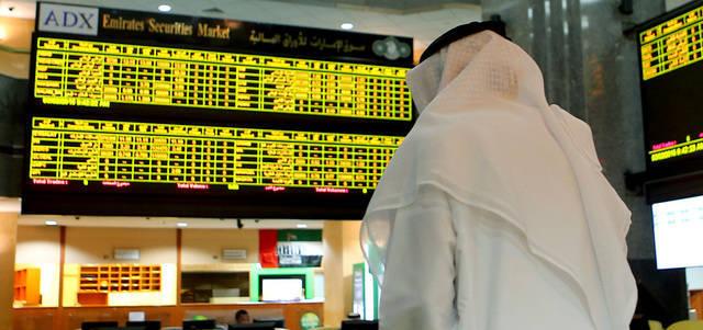مستثمر يتابع أسعار الأسهم بقاعة سوق أبوظبي للأوراق المالية
