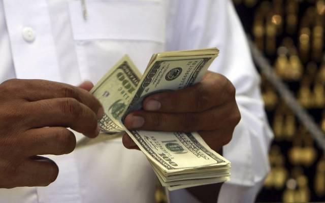 مواطن خليجي يُحصي نقود من فئة 100 دولار أمريكي