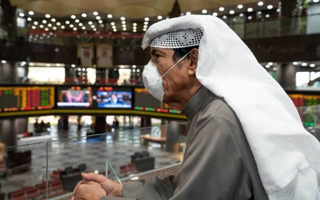 مستثمر يتابع التداولات ببورصة الكويت مرتدياً كمامة الوقاية من الفيروسات
