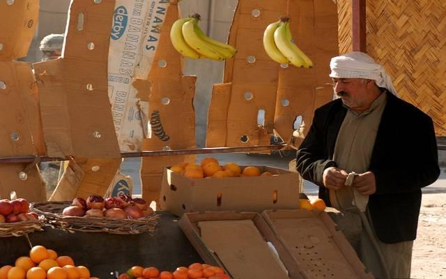 تاجر يبيع الفاكهة بأحد الأسواق العراقية