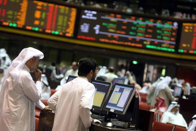 متعاملون يتابعون الأسعار بقاعة سوق الكويت المالي