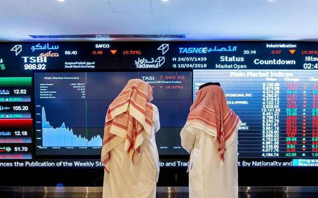 رجلان أمام شاشة بسوق الأسهم السعودية