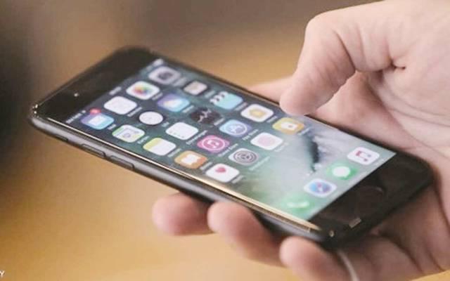 مستخدم يمسك بيده أحد الهواتف النقالة