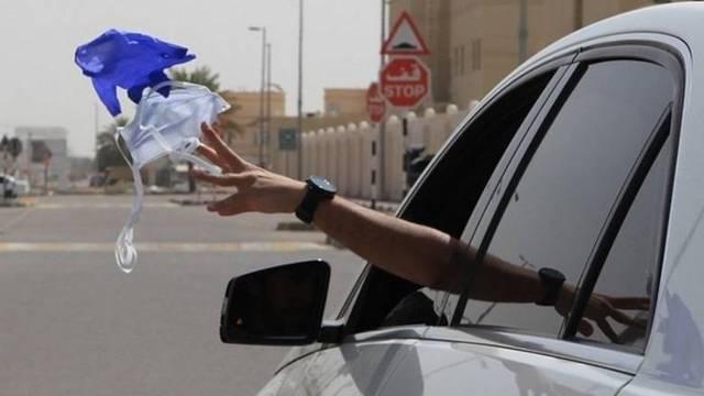 أحد قائدي السيارات يلقي بالكمامة في الطريق بعد استخدامها