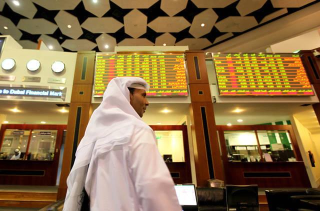 متعاملون يتابعون الأسعار بقاعة سوق دبي للأوراق المالية، الصورة أرشيفية