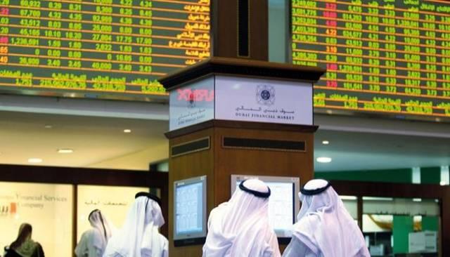 متعاملون يتابعون أسعار الأسهم بقاعة سوق دبي المالي